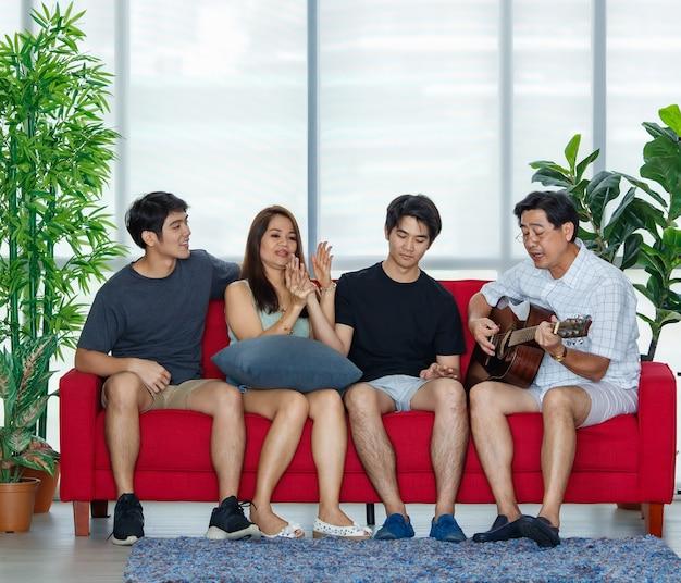 Vier leden aziatische familie bestaande uit ouders, twee volwassen zonen die tijd doorbrengen met gitaar spelen, samen zingen met geluk en gezelligheid op de bank tijdens vakanties in een comfortabele woonkamer thuis.