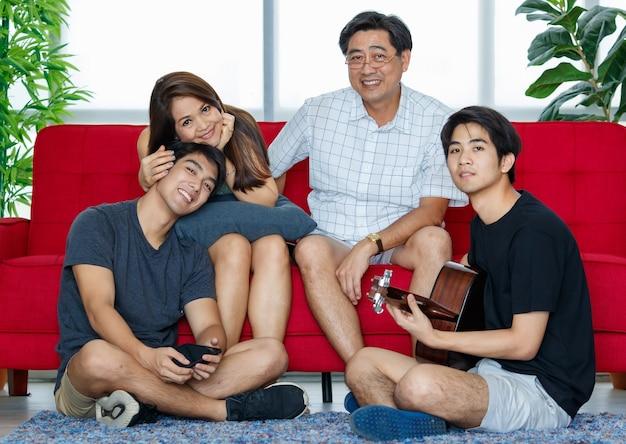Vier leden aziatische familie bestaande uit ouders, twee volwassen zonen die tijd doorbrengen met gitaar spelen, samen zingen met geluk op de bank tijdens vakanties in de woonkamer thuis. ze kijken naar de camera.