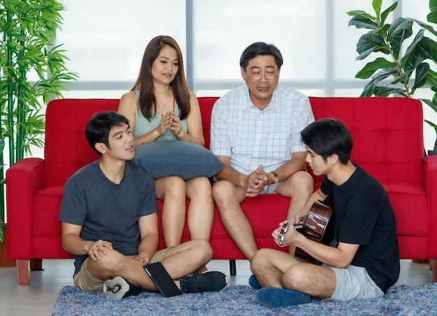 Vier leden aziatische gelukkige leuke familie tijd doorbrengen met gitaar spelen, samen zingen. ouders van de jaren 50 op de bank en twee volwassen knappe zonen die tijdens de vakantie op de vloer in de gezellige woonkamer thuis zitten.