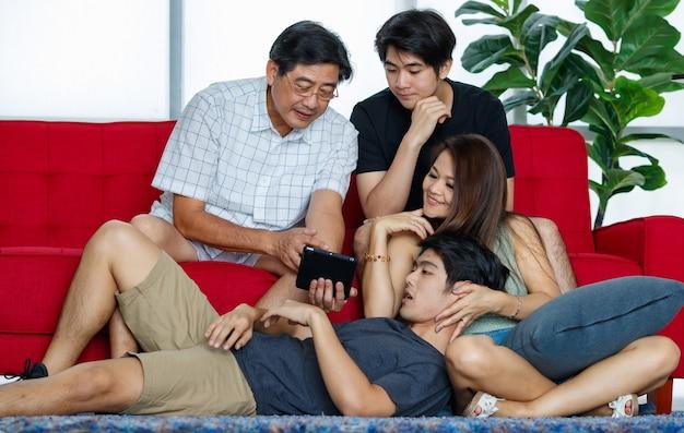 Vier leden aziatische leuke familie bestaat uit vader en moeder met twee volwassen zonen, tijd doorbrengen tijdens vakanties samen met geluk, ontspanning in de woonkamer thuis, gebruiken, kijken op tablet.