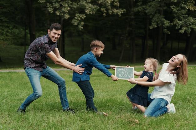 Vier ledenfamilie die pret hebben terwijl het spelen in het park
