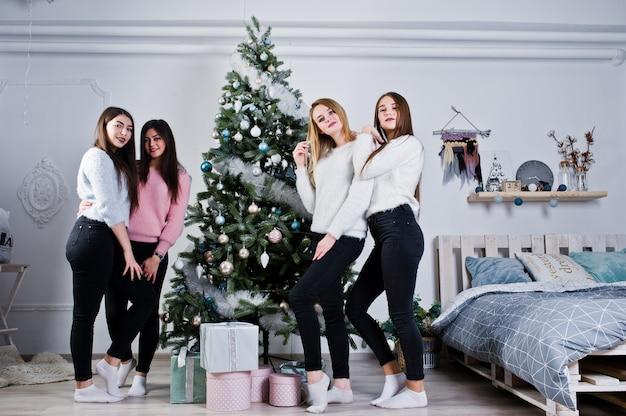 Vier leuke vriendenmeisjes dragen op warme sweaters, zwarte broek tegen boom met kerstmisdecoratie bij witte ruimte.
