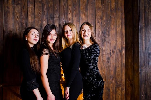 Vier leuke vriendenmeisjes dragen zwarte jurken tegen een grote lichte kerststerdecoratie op een houten muur