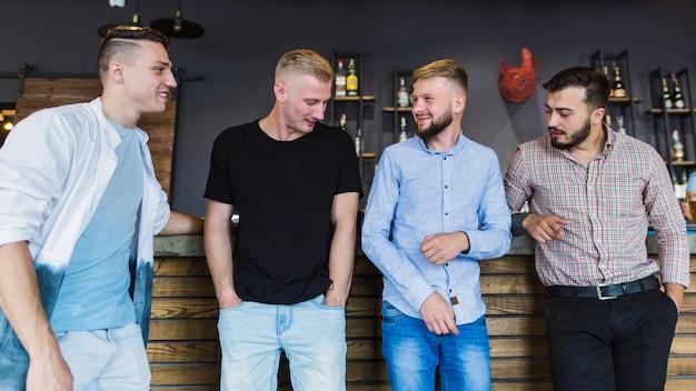Vier mannelijke vrienden in vrijetijdskleding die zich bij staafteller bevinden