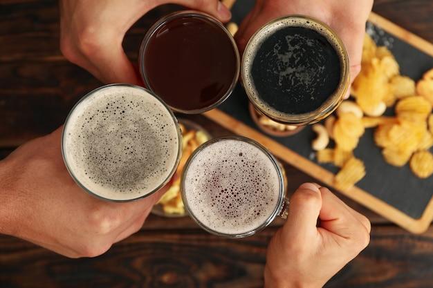 Vier mannen juichen met bier met hapjes