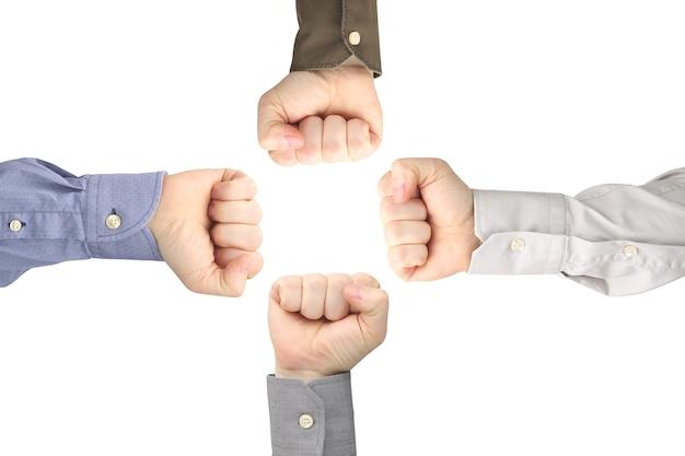 Vier mannenhanden gebald tot vuisten tegenover elkaar op een witte ruimte. de discussie en de relaties in de samenleving. diplomatie en gebarentaal tussen tegenstanders