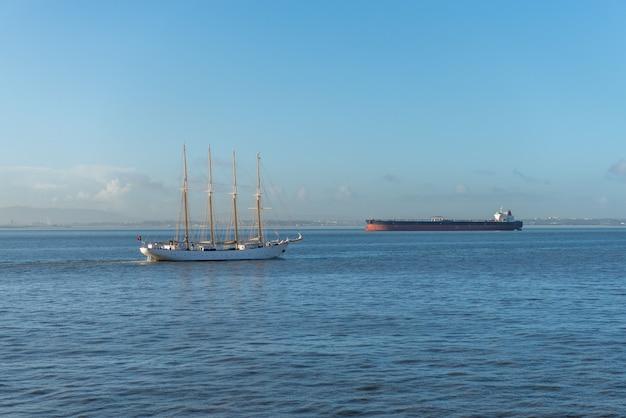 Vier masten zeilschip en vrachtschip op zee