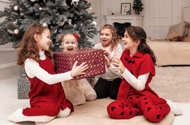 Vier meisjes in een kerstjurk verheugen zich met een kerstcadeaudoos