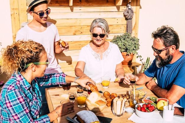 Vier mensen genieten van het ontbijt op het terras in het zonlicht. ouders met tienerzoon en grootmoeder. houten tafel met huisgemaakt gebak, fruit en koffie