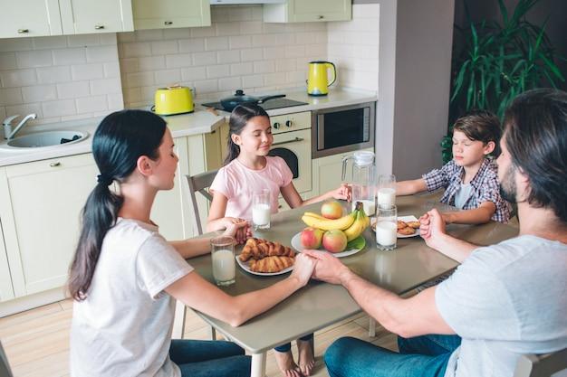 Vier mensen van het gezin zitten samen aan tafel en houden elkaars handen vast. ze houden de ogen gesloten. familie bidt.