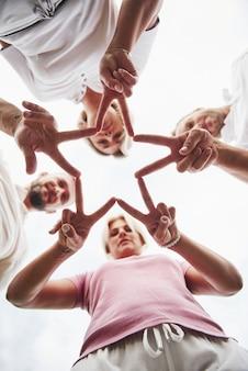 Vier mensen vouwen de handen in elkaar als teken van hun teamwerk