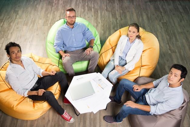 Vier mensen zitten op de zitzak stoelen rond de tafel