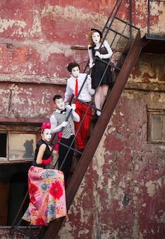 Vier mimespelers staan op de trap op een rode muur