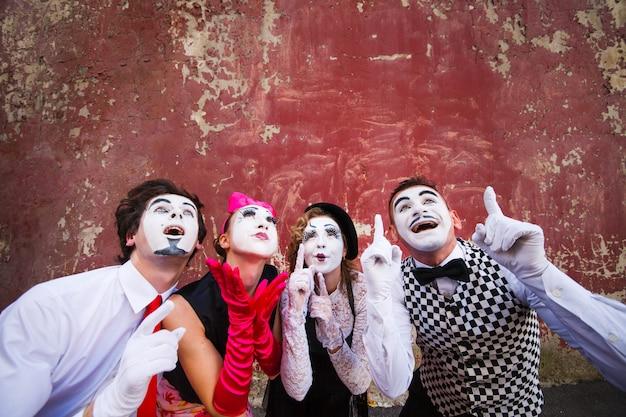 Vier mimespelers wijzen naar de top op een rode muur