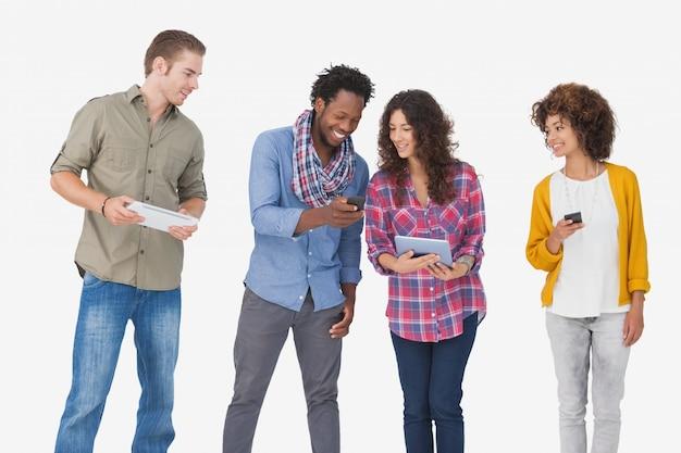 Vier modieuze vrienden die tablet bekijken en telefoons houden