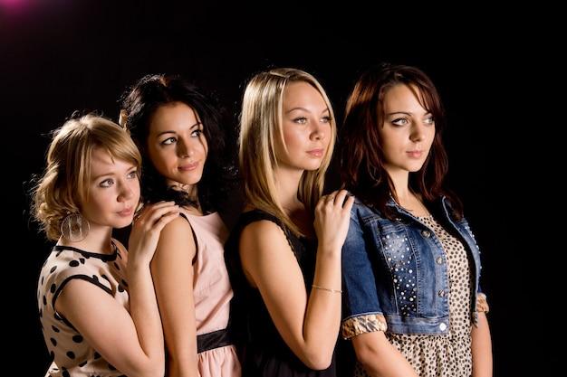 Vier mooie jonge vriendinnen poseren achter elkaar in een rij