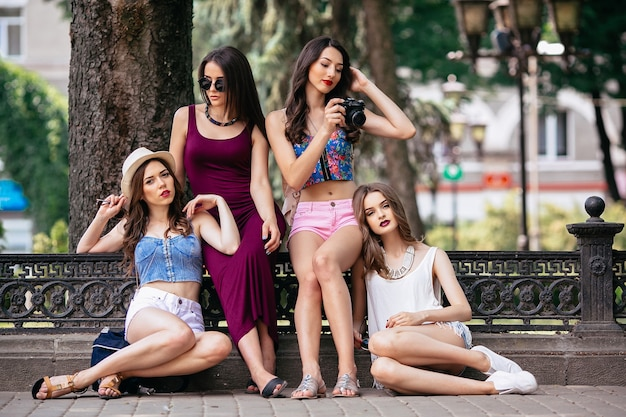 Vier mooie jonge vrouwen poseren in het park