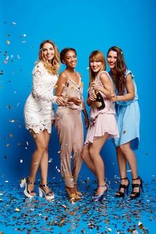 Vier mooie meisjes die bij partij over blauwe muur rusten