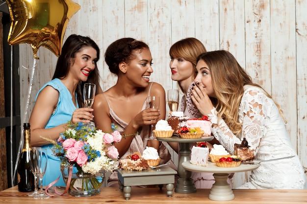 Vier mooie meisjes die bij partij over witte muur rusten