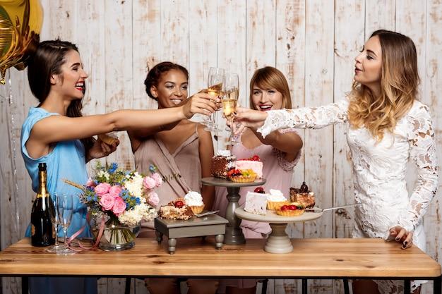 Vier mooie meisjes rammelende glazen met champagne op feestje.