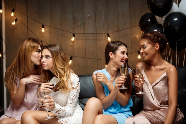 Vier mooie meisjes rusten op feestje.
