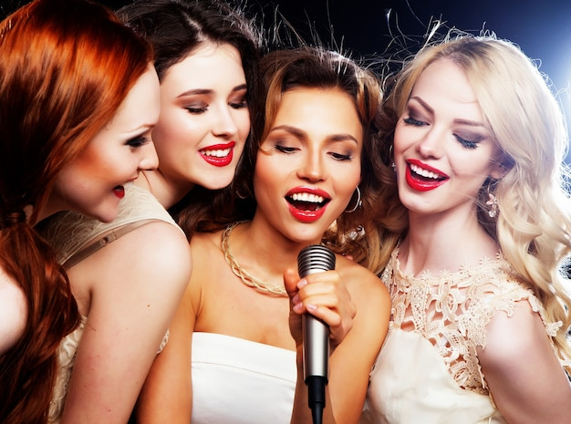 Vier mooie stijlvolle meisjes die karaoke zingen in de club