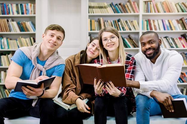 Vier multi-etnische vrolijke studentenvrienden in de bibliotheek, die boeken lezen, communiceren en samen tijd doorbrengen