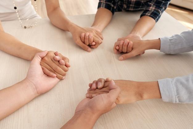 Vier onherkenbare mensen zitten aan tafel en houden elkaars handen in het midden