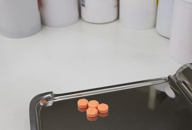 Vier oranje medische tabletten op half tellend geneesmiddeldienblad voor drogisterij