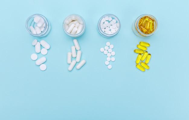 Vier pakketten met verschillende witte pillen en capsules op een witte achtergrond