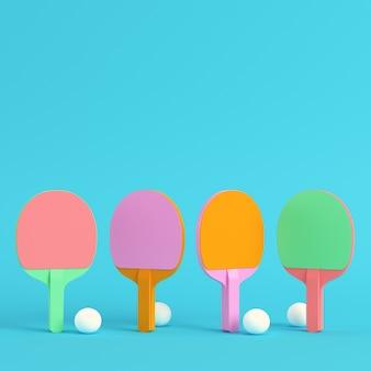 Vier pingpongrackets met ballen op heldere blauwe achtergrond in pastelkleuren