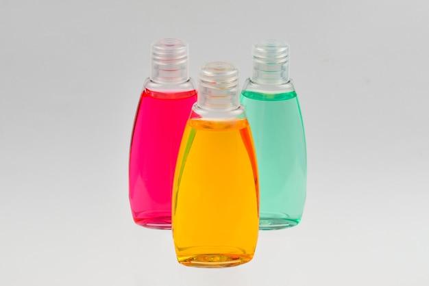 Vier plastic flessen met vloeibare gele, groene en rode zeep.