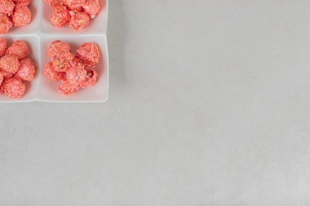 Vier porties met snoep beklede popcorn in een snackschotel op marmeren tafel.