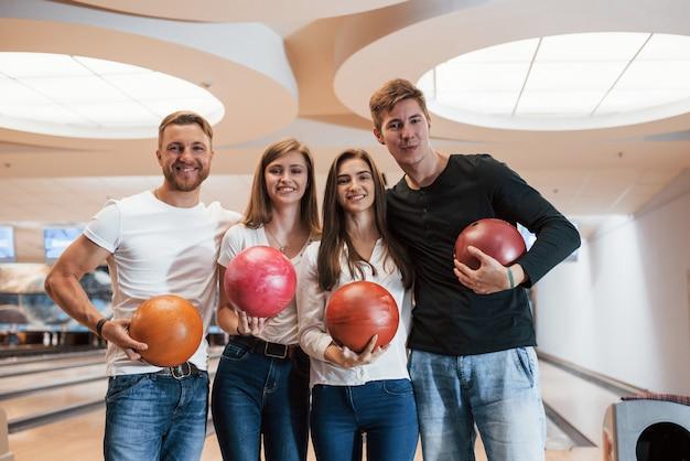 Vier positieve mensen. jonge, vrolijke vrienden vermaken zich in het weekend in de bowlingclub