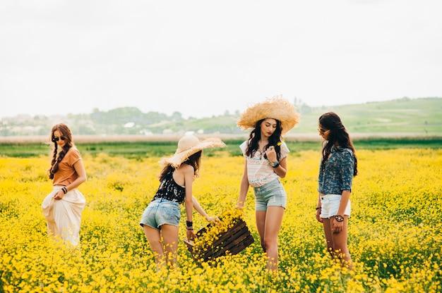 Vier prachtige hippie meisje in een veld van gele bloemen