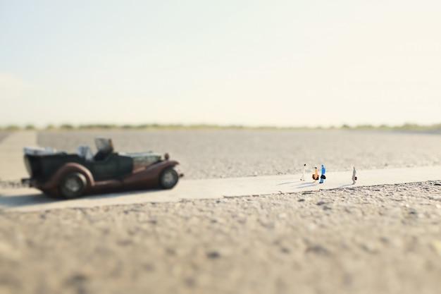 Vier reizigers (miniatuur) en een klassieke auto op landweg.