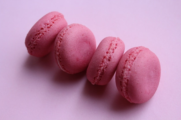 Vier roze makarons op een lichtrose achtergrond, minimaal voedselconcept