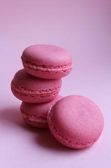 Vier roze makarons op een lichtrose achtergrond, zoet minimaal voedselconcept