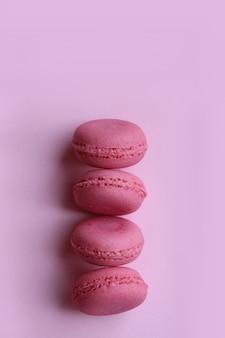 Vier roze makarons op een lichtrose achtergrond.
