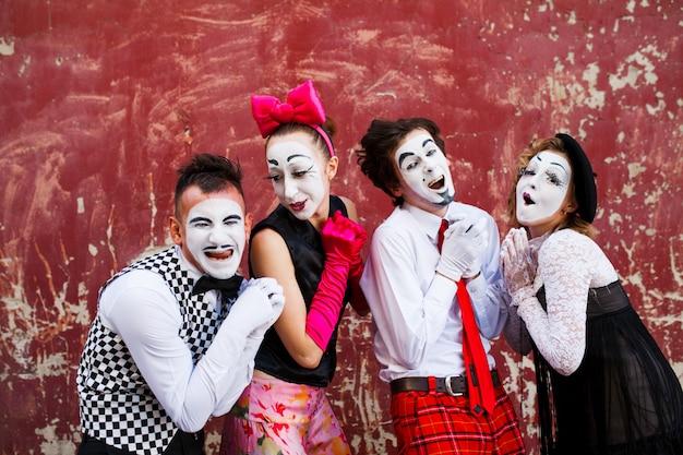 Vier schattige mimespelers staan op een rode muur