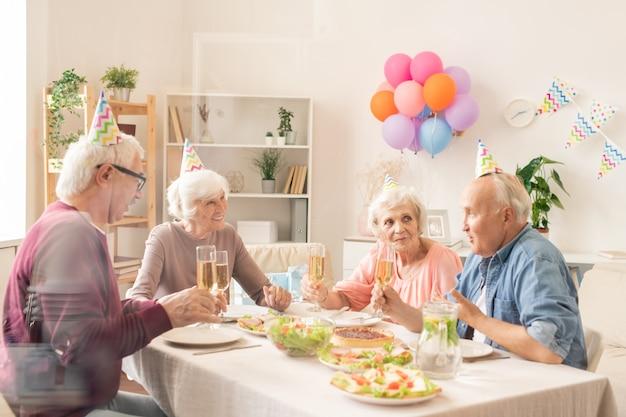 Vier senior vrienden met champagne zitten door feestelijke tafel tijdens thuis verjaardagsfeestje