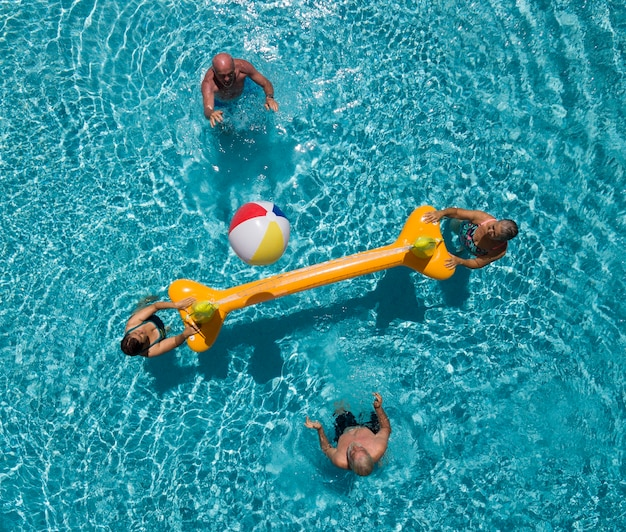 Vier senioren in het zwembad met opblaasbaar net en bal. twee oudere broers en hun vrouw hebben plezier. helder licht van de zon