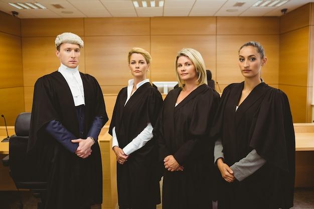 Vier serieuze rechters staan tijdens het dragen van gewaden