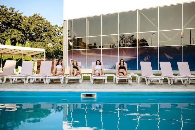 Vier sexy vrouwen vrije tijd op ligbedden bij het zwembad, uitzicht vanaf het water. dames ontspannen bij het zwembad op zonnige dag, zomervakantie van vriendinnen