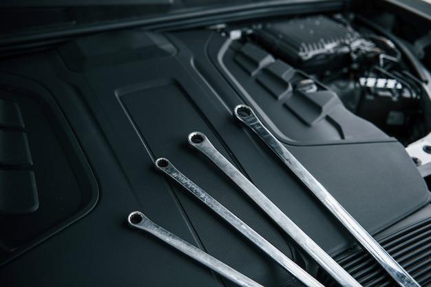 Vier sleutels. reparatiehulpmiddelen die onder de motorkap van auto leunen. zilverkleurig