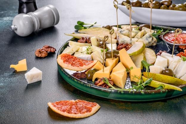 Vier soorten kaas snijden: geiten, parmezaan, camembert en brie met plakjes peer en gedroogde grapefruit en microgreens. lekker gezond tussendoortje