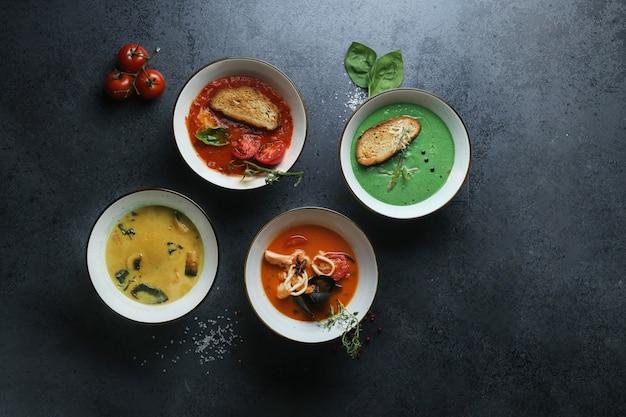 Vier soorten roomsoepen gemaakt van tomaten, champignons, zeevruchten en basilicum