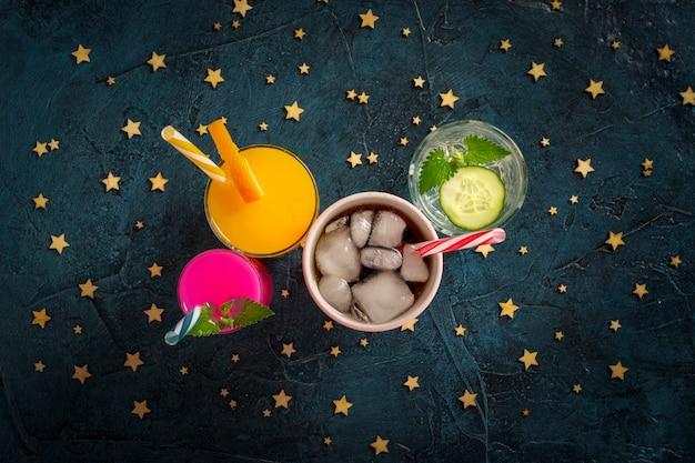 Vier soorten verfrissende drankjes met ijs op een donkerblauw oppervlak en ijsblokjes. concept nachtclub, nachtleven, feest, dorst. sinaasappel, munt en komkommer, aardbei, cola. plat lag, bovenaanzicht