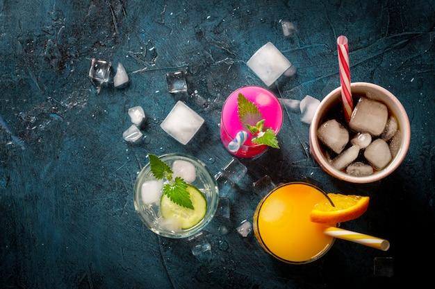 Vier soorten verfrissende drankjes met ijs op een donkerblauwe achtergrond en ijsblokjes. concept nachtclub, nachtleven, feest, dorst. sinaasappel, munt en komkommer, aardbei, cola. plat lag, bovenaanzicht