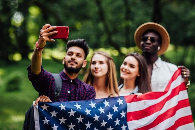 Vier studenten maken selfie in de buurt van campus op universiteit
